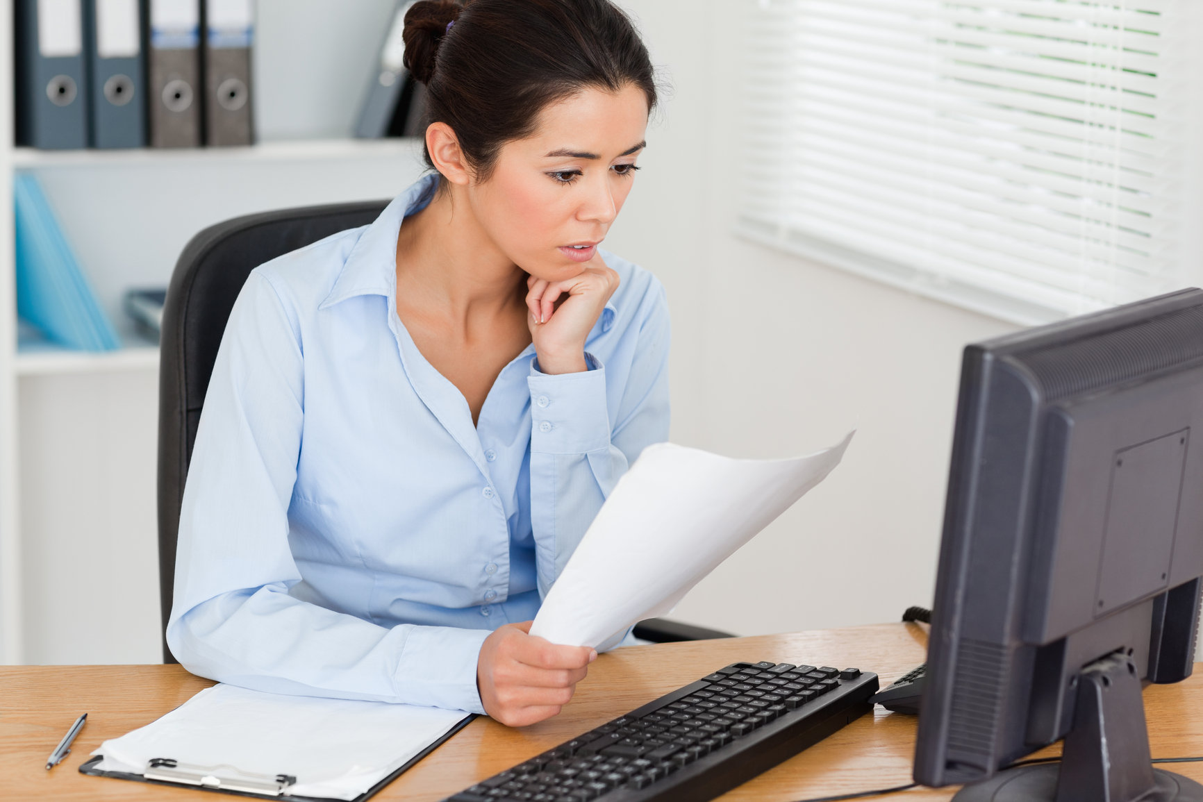 Gorgeous woman looking at a computer screen while holding a sheet of paper at the office